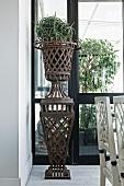 Planter on rusty, metal lattice plinth in loggia-style room