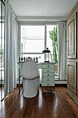 White, classic shell chair at desk in narrow room with floor-length curtains on windows