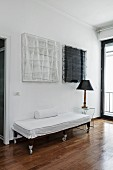 Couch on castors with white loose cover next to table lamp on transparent side table below black and white artworks on wall