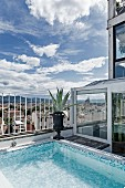 Pool with mosaic tiles in various shades of blue on penthouse roof terrace with view of Florence