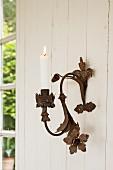 Brennende Kerze in Metall Wandkerzenleuchter mit Blumenelementen im Vintage Stil, an heller Holzwand