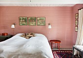 Double bed with white bedspread flanked by sconce lamps on wooden wall painted pink in rustic bedroom