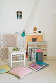 Old, white stool amongst cushions on white board floor, books and pictures leaning against white wall next to gathered lace curtain