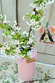 Wild cherry blossom in pink milk can on antiquarian botanical book in front of postcard of the Madonna on white wooden wall