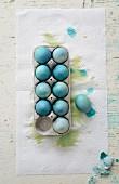 Blau gefärbte Eier in Eierkarton auf Küchenkrepp