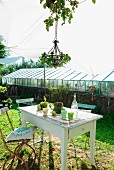 Old garden chairs with cushions at rustic garden table with beakers and vintage lemonade bottle below chandelier wreathed in ivy and awning; greenhouse in background