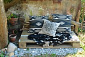 Bench made from old wooden pallet with goat-skin rug and ethnic-style cushions
