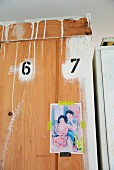 Back view of wooden wardrobe with painted numbers above postcard stuck on with yellow washi tape