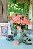 Salmon pink dahlias in green ceramic jug next to hydrangea in blue china teacup and picture hand-crafted from old postcard