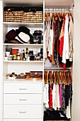 Fashion accessories on shelves and clothing on coat hangers in fitted wardrobe with open door