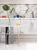 Dining table, wire chairs and arrangement of palm fronds in front of kitchen counter with mottled marble worksurface