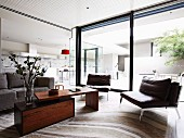 Leather armchairs, adjustable coffee table and sliding glass wall in open-plan interior with view into courtyard