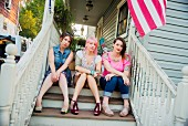 Portrait of young female friends sitting on porch steps