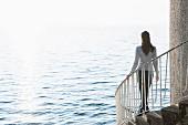 Young woman walking down spiral stairs, Lake Constance, Lindau, Bavaria, Germany