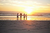 Family holding hands on beach, Cape Town, South Africa