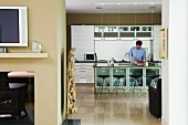 Man behind counter in open-plan kitchen with walls painted sandy beige
