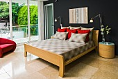 Scatter cushions on double bed with wooden frame and headboard, designer table lamp on oval bedside cabinet against black-painted wall, sand-coloured limestone floor, glass wall to one side