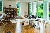 Bright office with designer desks, drawing table and glass sliding doors