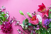 Various flowers - lilies, clustered bellflower, peonies, phlox - on pink surface