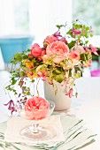 Pink rose in champagne saucer on stacked napkins and bouquet of fragrant English roses and clematis in white vase on table