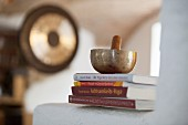 Singing bowl and striker on stacked books on masonry surface