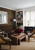 Sitzgruppe mit Sofa, Antiksesseln und Geflecht-Tischen vor braun getönter Rückwand