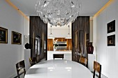 Magnificent crystal lamp above white, oval dining table in front of doorway leading to modern kitchen with wood-veneer fronts
