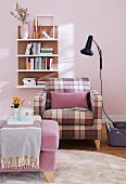 A comfortable armchair with a checked cover and a purple cushion opposite an upholstered stool with a black wall light and a shelf on a pale pink wall