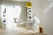 Sonnendurchflutetes Arbeitszimmer mit gläsernem Schreibtisch und weissen Designerstühlen; zwei luftige Regale sorgen für Ordnung