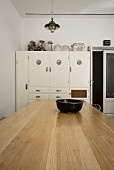 Vintage kitchen cupboard against white wall; pale, solid wood table in foreground