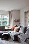 Moderne Wohnzimmerecke - Polstersofa mit grauem Samtbezug und runder Schemel mit Kissen auf Teppichboden, im Hintergrund Sprossenfenster und Blick in Garten