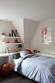 Einzelbett vor weisser, eingebauter Ablage als Tisch und vor Regalböden mit Stofftieren