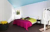 Schlafbereich mit weissen Vorhängen abgetrennt, Doppelbett mit farbigen Tagesdecken auf dunklem Teppichboden in dreieckigem Schlafzimmer, Stehleuchte zwischen Fenstern, im Vordergrund Kleiderständer mit weisser Kleidung