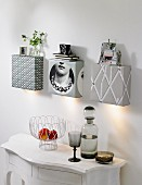 A fruit bowl and a smoky glass bottle and a matching stem glass on a white wall table with homemade wall lights covered with wallpaper that also serve as shelves hung above it