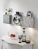 Selbstgebaute Wandleuchten, auch als Ablage, mit Tapete beklebt, weisse Wandkonsole mit Obstschale und rauchfarbener Glasflasche mit passendem Stielglas