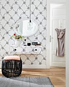 A make-up table and a wall creating a graphic element – Scandinavian, vintage-style patterned wallpaper on both the wall and the make-up table with a black wicker stool in front of it