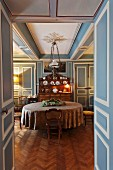 Dining room with blue and white wood panelling, round table, dresser and collection of antique chairs