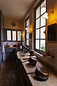 French kitchen counter with blue doors and shallow stone sink with brass taps in foreground