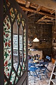 Open door with floral painted glass panels and view of sky blue garden furniture in converted stable