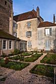 Rechteckige Beete in Kiesfläche vor historischem Gebäudekomplex in der Bourgogne