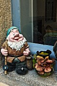 French garden gnome and vase decorated with applied ceramic flowers on windowsill
