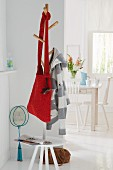 A red knitted shoulder bag on a clothes tree