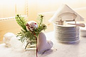 Silver Christmas baubles, fir twigs and fabric love-heart decorating festive buffet