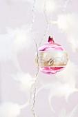 Gold- und pinkfarbene Weihnachtskugel an gedrehtem Band mit Federschmuck