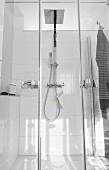 Verglaste Duschkabine mit zweiteiliger Pendeltür, Regendusche und Handbrause an weissen Wandfliesen