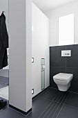 A room divider between a shower and toilet with a built in toilet paper holder and lighting with large black tiles on the floor and halfway up the wall