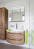 A curved, oak-style washstand on a white tiled wall with a three-section mirrored cabinet above it with an integrated strip light