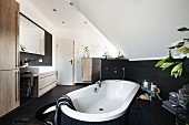 A bathtub positioned at an angle in the room under a vaulted roof with brown tiles halfway up the wall opposite a trough-style washstand and a large mirror on the wall in a modern bathroom