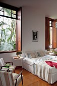 Comfortable double bed against wall, armchairs next to window with wooden interior shutters and view of palm trees