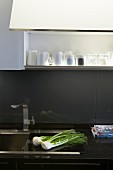 Detail of kitchen counter with stainless steel sink in black worksurface; grey painted glass splashback below open-fronted overhead cabinet with interior light